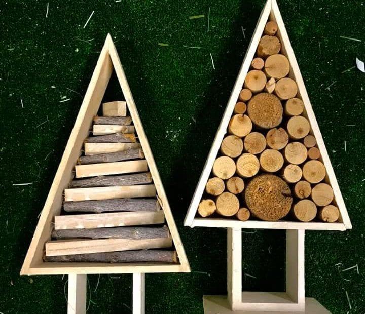 2 nowoczesne choinki wykonane z drewnianych listwek umieszczone a zielonym tle