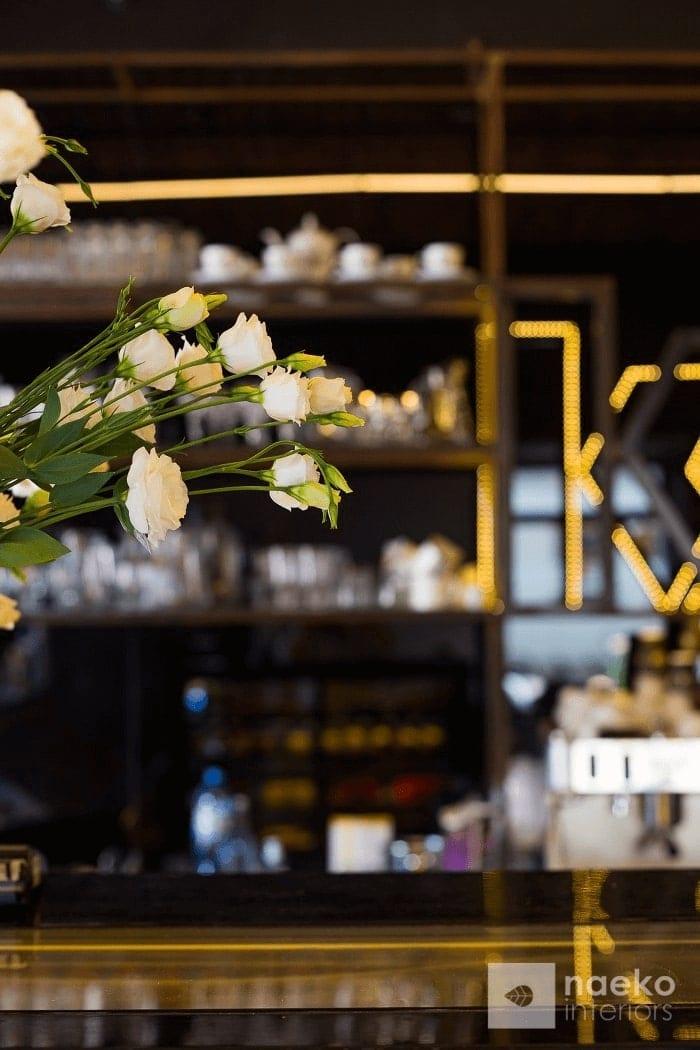 Detal architektoniczny ekownętrza kawiarni z regałem wykonaym w stalowej podkunstrukcji zamontowanym na tle czarnej ściany i białymi kwiatami