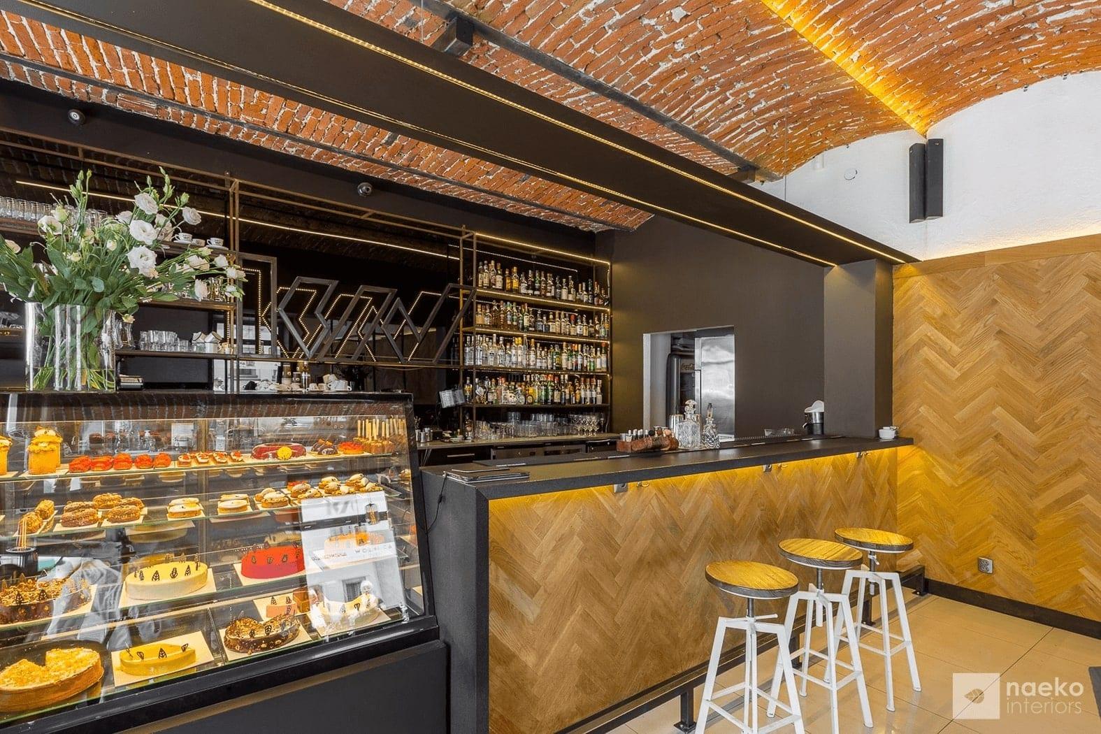 Widok lady barowej ekokawiarni wykończonej drewnianą okładziną z kamiennym blatem oraz tylną, czarną ścianą za barem z ustawionymi na konstrukcji stalowej produktami