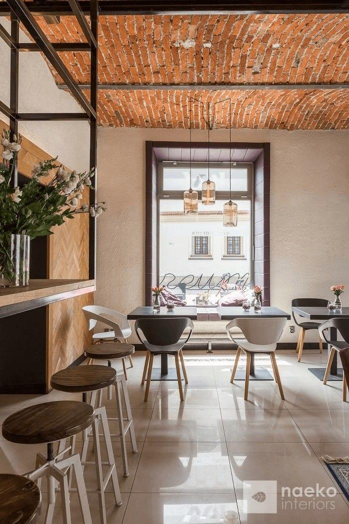 Projekt wnętrza kawiarni less waste z centralnym widokiem na duże okno, z ceglanym stropem, drewnianą okładziną na ścianie po lewej stronie i dostawionym do niej industrialnym blatem