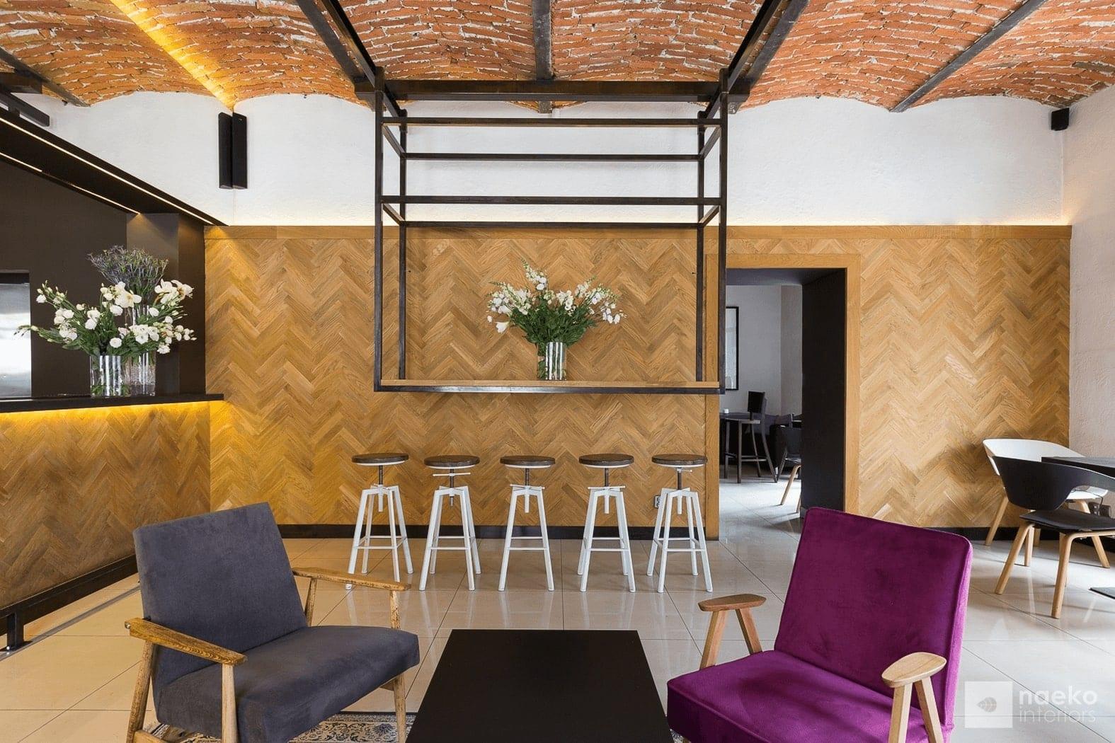 Projekt wnętrza ekokawiarni, z ceglanym stropem, drewnianą okładziną na ścianie, centralnie zlokalizowanym stolikiem kawowym z 2 fotelami retro:burgundowym i ciemnoszarym