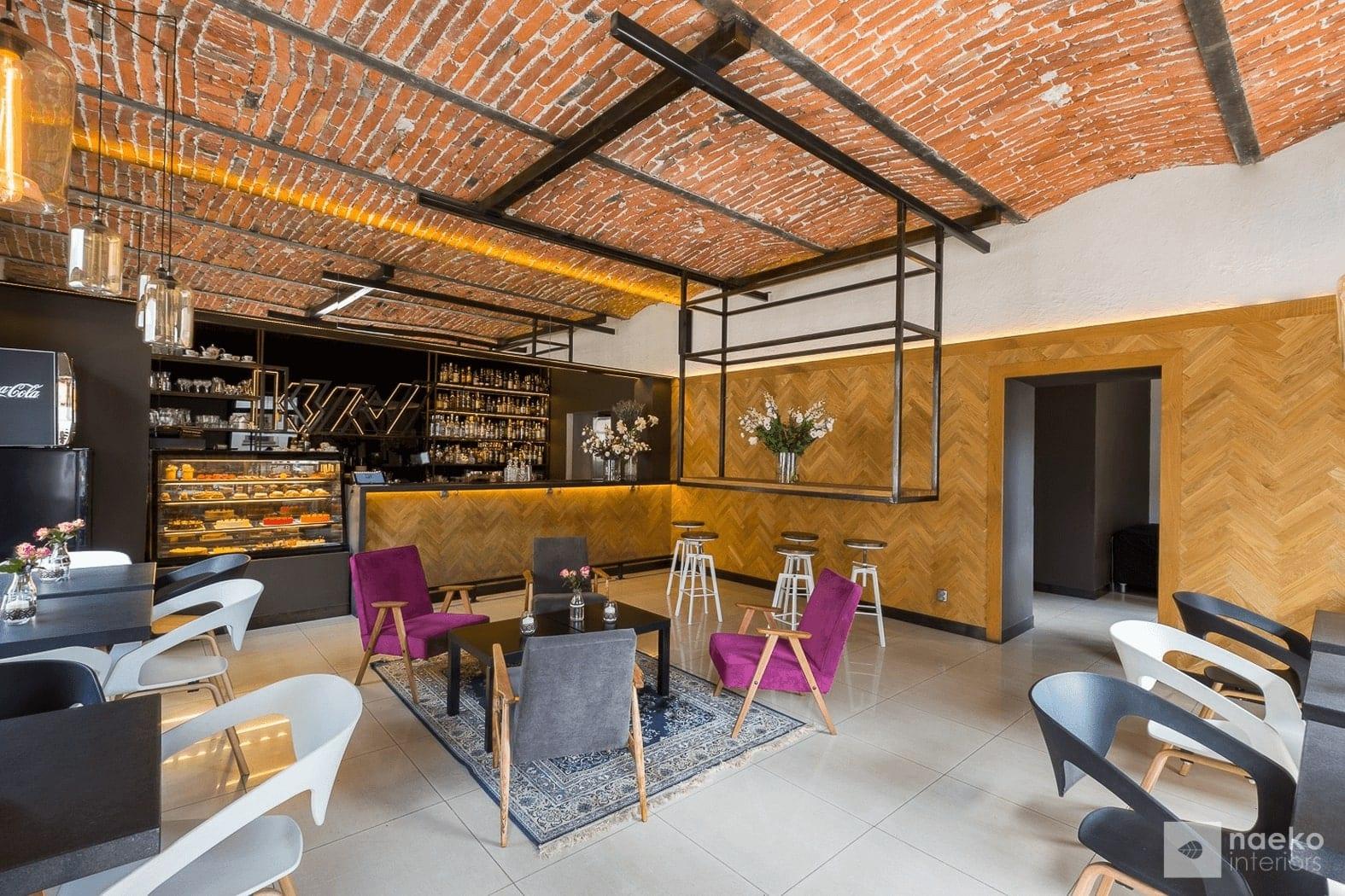 Projekt wnętrza ekokawiarni, z ceglanym stropem, drewnianą okładziną na ścianie, centralnie zlokalizowanym stolikiem kawowym z burgundowymi fotelami i tureckim dywanem vintage