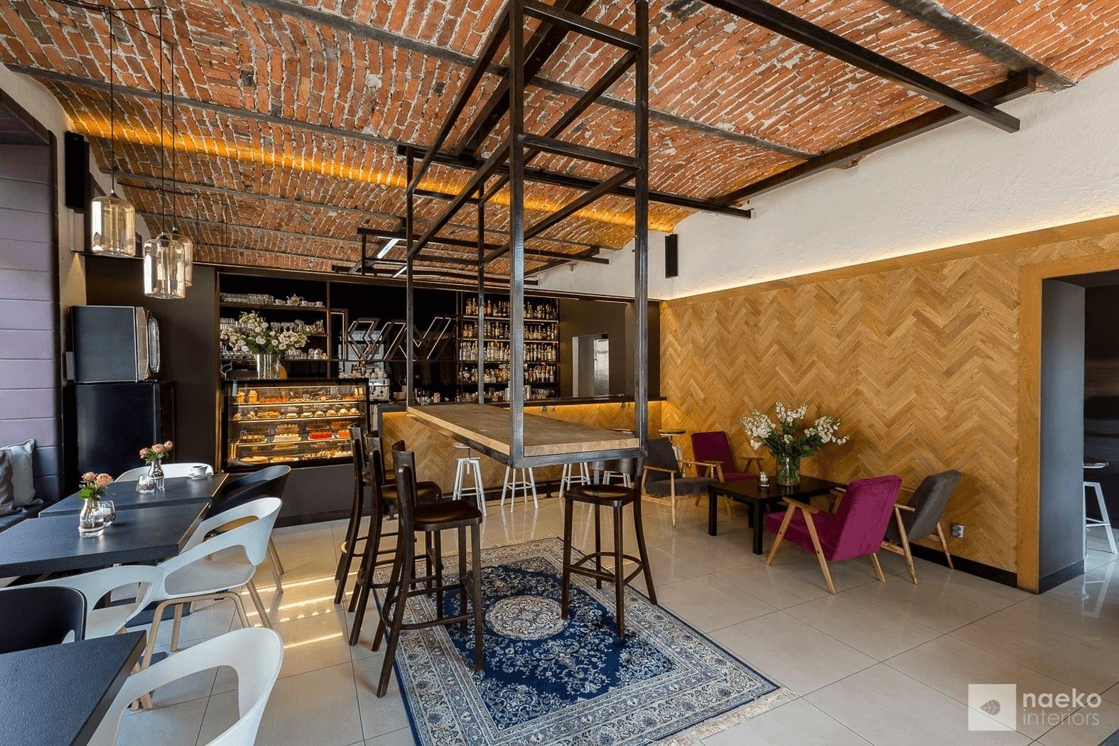 Projekt wnętrza ekokawiarni, z ceglanym stropem, drewnianą okładziną na ścianie, centralnie zamontowanym blatem na stalowej podkonstrukcji, wysokimi stołkami barowymi i dywanem vintage