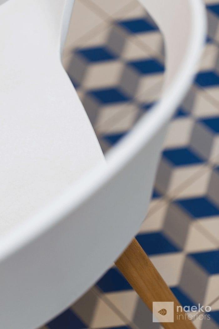 Kuchnia w stylu skandynawskim detal krzesła na tle geometrycznego wzoru posadzki