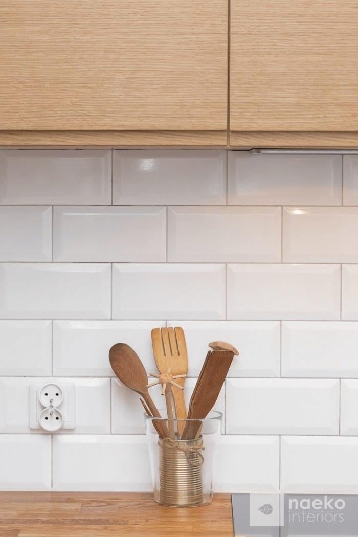 Kuchnia w stylu skandynawskim detal wykończenia z drewnianymi akcesoriami kuchennymi na tle białych płytek ściennych w stylu retro