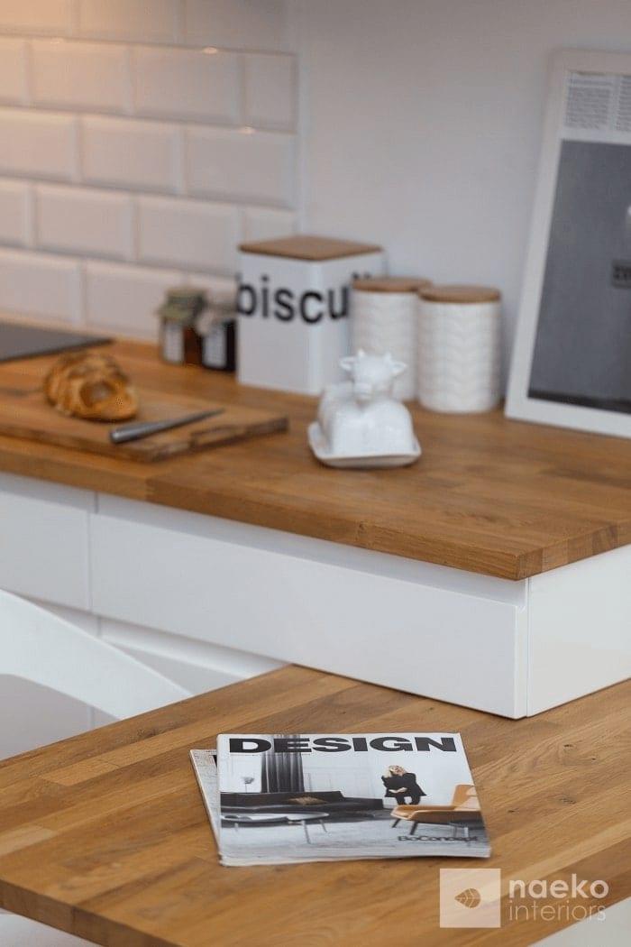Kuchnia w stylu skandynawskim detal zamocowania podwieszonego blatu ze stojącą na nim oryginalną maślniczką oraz akcesoriami kuchennymi