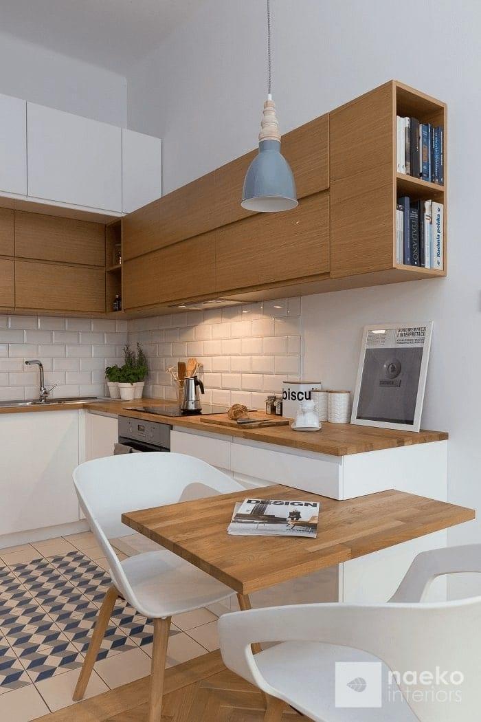 Projekt kuchni w stylu skandynawskim z białą zabudową i drewnianymi elementami oraz nadwieszonym blatem