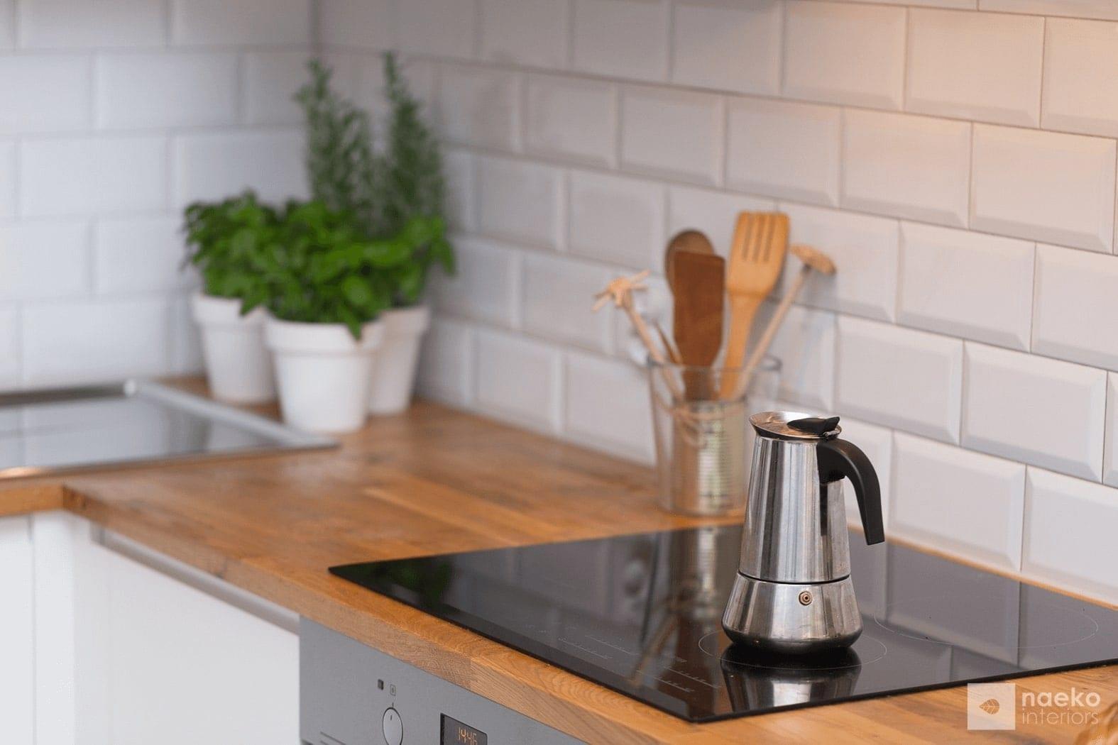 Kuchnia w stylu skandynawskim detal blatu i ściany z białych cegiełek oraz imbrykiem kawowym na pierwszym planie