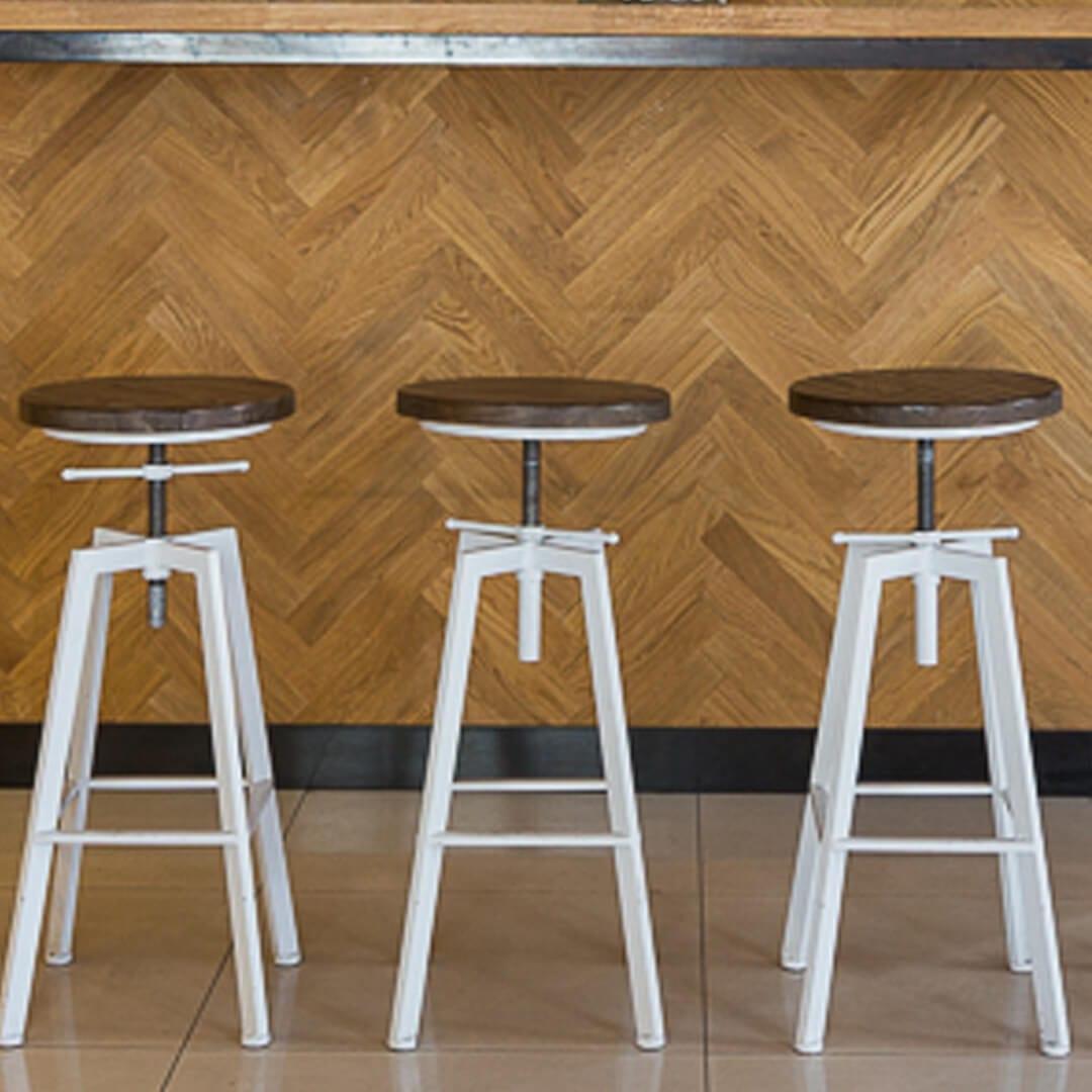 Detal wnętrza kawiarni less waste- z drewnianą okłądziną na ścianie i 3 industrialnymi hockerami barowymi