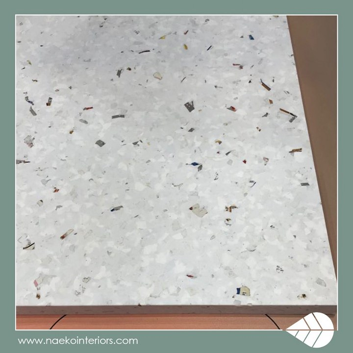 Płyta wykonana ze zrecyklingowanego plastiku w kolorze białym, o niejednorodnej strukturze z wielobarwnymi drobinkami