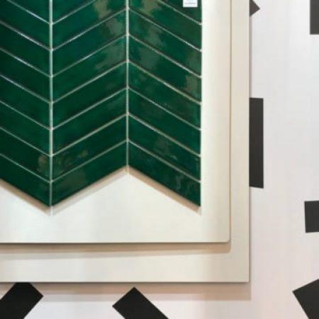Abstrakcyjna kompozycja kafelków ceramicznych w kolorze butelkowej zieleni w ukłądzie w jodełkę