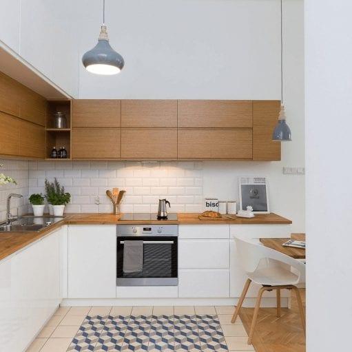 Projekt kuchni w stylu skandynawskim z białą zabudową i drewnianymi elementami oraz geometryczną mozaiką na posadzce w kolorze szaro-kremowo-granatowym