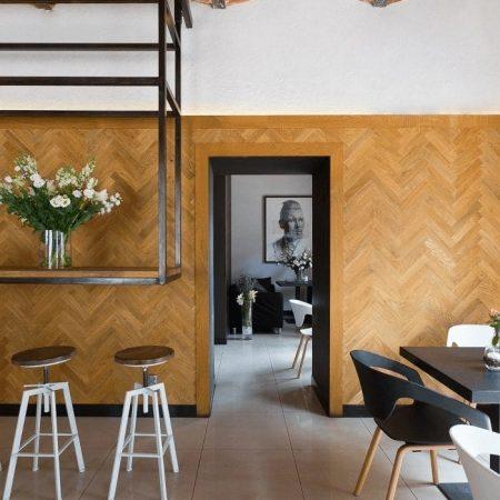 Projekt wnętrza kawiarni z drewnianą okładziną na ścianie i podkonstrukcją stalową podwieszanego blatu na którym stoi wazon z białymi kwiatami, pod nim 2 białe,industrialne hockery barowe