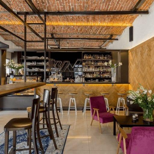 Projekt wnętrza ekokawiarni, z ceglanym stropem, drewnianą okładziną na ścianie, centralnie zamontowanym blatem na stalowej podkonstrukcji, wysokimi stołkami barowymi i fotelamivintage