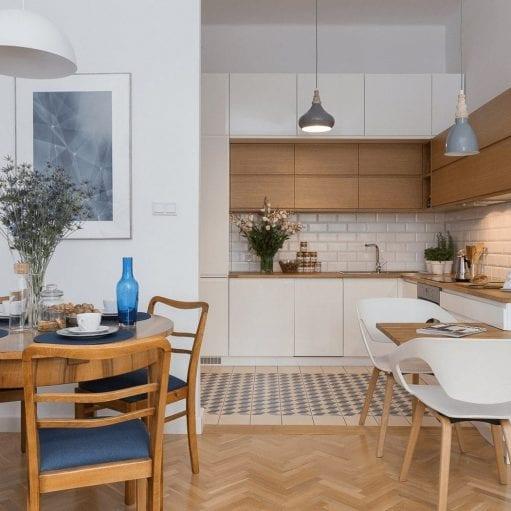 Projekt kuchni w stylu skandynawskim z białą zabudową i drewnianymi elementami oraz starym stołem i krzesłami w stylu vintage i granatowymi dodatkami