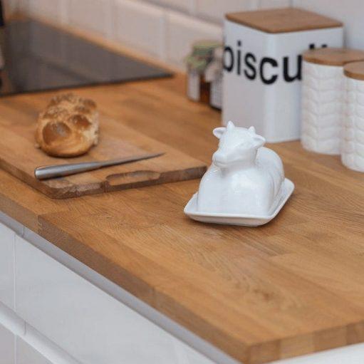 Kuchnia w stylu skandynawskim detal blatu ze stojącą na nim oryginalną maślniczką oraz akcesoriami kuchennymi