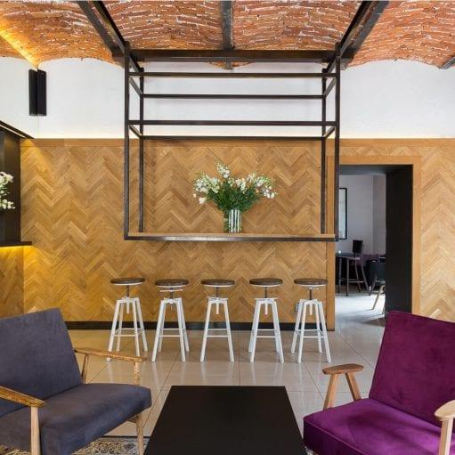Projekt wnętrza kawiarni less waste, z ceglanym stropem, drewnianą okładziną na ścianie, industrialnym blatem na stalowej podkonstrukcji i fotelami vintage